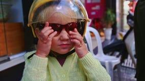 Девушка крупного плана маленькая белокурая в шлеме пробует дальше солнечные очки магазином сток-видео