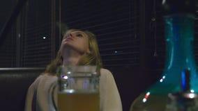 Девушка курит кальян и выпивает пиво на ночном клубе сток-видео