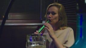 Девушка курит кальян и выпивает пиво на ночном клубе видеоматериал