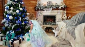 Девушка кладет вниз подарок под рождественскую елку, ребенка подготавливает сюрприз для родителей, Рожденственскую ночь Нового Го сток-видео