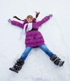 Девушка кладя в форму звезды в снеге Стоковые Изображения