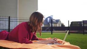 Девушка лежа на траве с компьтер-книжкой, сторона битника сток-видео
