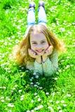 Девушка лежа на траве на grassplot, зеленой предпосылке Ребенок наслаждается погодой весны солнечной пока лежащ на луге расцвет стоковое фото