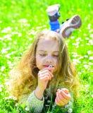 Девушка лежа на траве, grassplot на предпосылке Девушка на мечтательной стороне держит цветок маргаритки Ребенок наслаждается пог Стоковое Фото