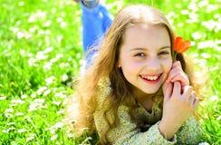 Девушка лежа на траве, grassplot на предпосылке Ребенок наслаждается днем весны солнечным пока лежащ на луге с цветками сезонно стоковые изображения rf