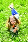 Девушка лежа на траве, grassplot на предпосылке Ребенок наслаждается днем весны солнечным пока лежащ на луге с цветками сезонно стоковые фотографии rf