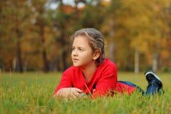 Девушка лежит на зеленой траве в парке Стоковая Фотография