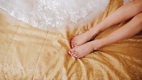 Девушка лежит на кровати Конец-вверх красивых ног r сток-видео