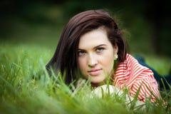 Девушка лежит на лужайке Стоковые Изображения RF