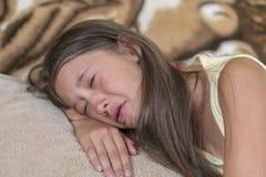 девушка лежит на софе и плачет Маленькая девочка задушевно плачет Концепция оскорбления, депрессии и misunderstan ребенка стоковая фотография