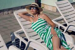 Девушка лежит на шезлонге в зеленом striped платье Стоковые Изображения RF