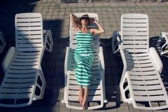Девушка лежит на шезлонге в зеленом striped платье Стоковая Фотография RF