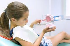 Девушка 10 лет в зубоврачебном стуле, с зубной щеткой Концепция медицины, зубоврачевания и здравоохранения стоковая фотография rf