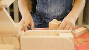 Девушка 10 лет старого молотка ноготь в кусок дерева в деревянной мастерской Дети в плотничестве 4K сток-видео
