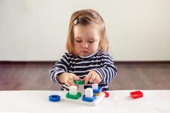 Девушка 1,5 лет с длинными волосами в striped платье сидит на таблице и игры с превращаться забавляются стоковое фото rf