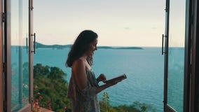 Девушка листая через книгу на фоне океана видеоматериал