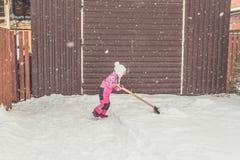 Девушка, лопаткоулавливатель младенца большой извлекает снег из пути в задворк на гараже стоковое фото rf