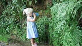 Девушка льет воду в стекло на источнике акции видеоматериалы