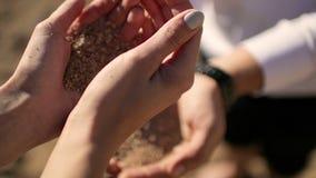 Девушка льет песок в руках человека сток-видео