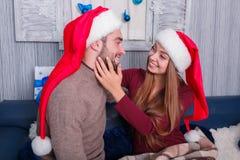 Девушка любяще смотрит парня, касаясь его стороне, улыбки парня назад Атмосфера рождества indoors стоковое изображение rf
