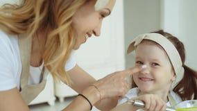 Девушка мажет нос маленькой девочки с мукой видеоматериал