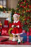 Девушка маленького ребенка веселого рождества и счастливых праздников милая украшает рождественскую елку внутри помещения стоковая фотография rf