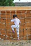 Девушка маленького ребенка вида сзади на спортивной площадке играя на взбираясь сети веревочки стоковое изображение