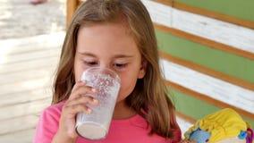 Девушка маленького ребенка выпивает ванильный коктейль молока акции видеоматериалы