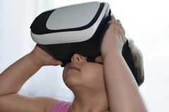 Девушка маленького ребенка играет игру с стеклами виртуальной реальности на белой предпосылке, увеличенной реальности, шлеме, ком стоковая фотография rf