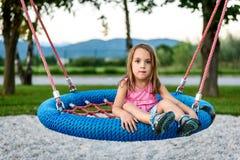 Девушка маленького ребенка на качании гнезда сети паука на спортивной площадке Стоковое фото RF