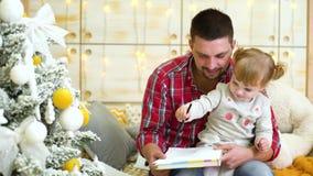 Девушка малыша сидя на ее подоле отца и рисует с карандашем около рождественской елки акции видеоматериалы