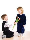 девушка мальчика дает тюльпаны Стоковая Фотография