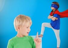 Девушка мальчика и супергероя с голубой предпосылкой Стоковое Изображение RF