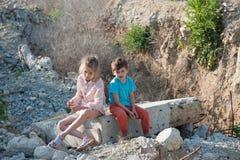 Девушка мальчика 2 плохая детей беженца на построении руин разрушенном путем взрывать стоковое фото
