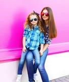 Девушка матери и ребенка в checkered рубашках, солнечных очках в городе на красочной розовой стене стоковое фото rf