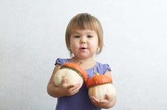 Девушка маленького ребенка держа 2 декоративных тыквы Стоковая Фотография RF