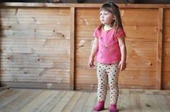 Девушка маленького ребенка на деревянной предпосылке Стоковые Изображения RF