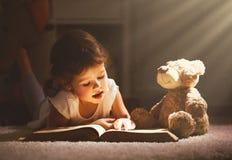 Девушка маленького ребенка читает книгу в вечере в темноте с a к Стоковые Фотографии RF