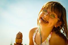 Девушка малыша есть мороженое на пляже Стоковое Изображение RF