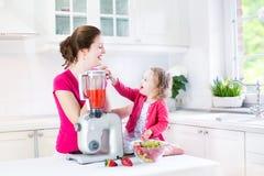 Девушка малыша и ее мать делая свежую клубнику Стоковая Фотография