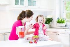 Девушка малыша и ее мать делая свежую клубнику Стоковое Изображение