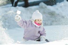 Девушка малыша меча вверх по естественному снегу с пластмассой стоковые изображения