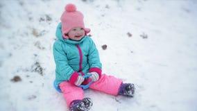 Девушка малыша нося теплый костюм снега и связанную пинком шляпу сидит на скелетонах поддонника Милый ребенок наслаждаясь зимой O акции видеоматериалы
