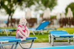 Девушка малыша сидя на sunbed бассейном Стоковая Фотография