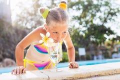 Девушка малыша с коктеилем в тропическом бассейне пляжа стоковые изображения rf