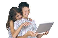 Девушка & мальчик смотря компьтер-книжку Стоковая Фотография