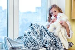 девушка медведя милая обнимая меньший игрушечный Милый младенец в комнате сидит на окне в зиме стоковые фото