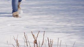 Девушка медленно идет в снег на солнечный день акции видеоматериалы