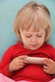 девушка меньшее играя touchphone Стоковые Изображения RF