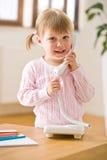 девушка меньший усмехаться телефона салона Стоковое Фото